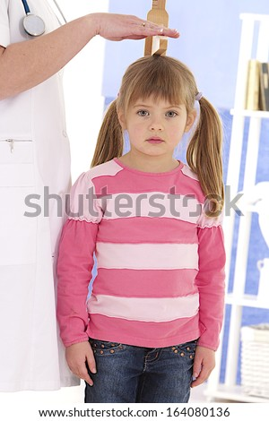 Pediatrician measure height of little girl at medical office  - stock photo