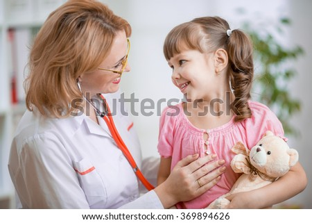 Pediatrician talking positively with kid - stock photo