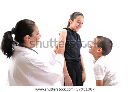 Pediatrician with stethoscope giving an injection in arm to a teenager while all having fun - MEDICAL IMAGES.