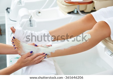 pedicure aplying nourishing moisturizer mask in legs of woman in nails salon