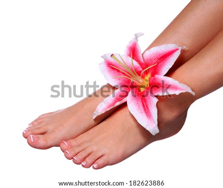 Pedicure. Beautiful female feet with french manicure and pink lily flower isolated on white. Nail care. Spa Salon - stock photo