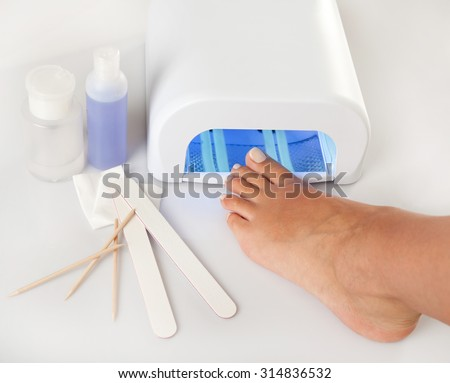 Pedicure foot and nail treatment with cosmetic products and UV lamp - stock photo