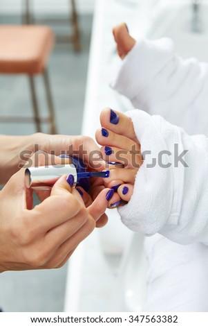 Pedicure nails polish blue in nail salon after sofa chair bath - stock photo