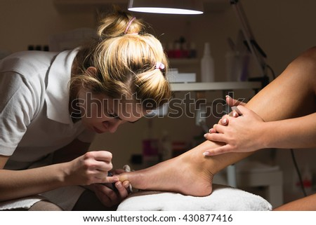 Pedicure treatment in beauty salon. Photographed in ambient light - stock photo