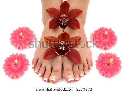 Pedicured feet with beautiful fresh orchids and aromatic flower candles - stock photo