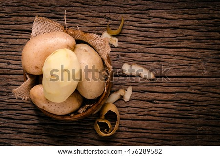 Peel fresh potatoes in wooden bowl. Raw organic potatoes on old wooden background. - stock photo