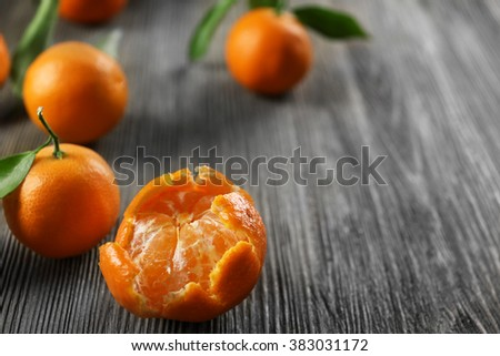 Peeled fresh tangerines with leaves and ripe mandarins on wooden table, closeup - stock photo