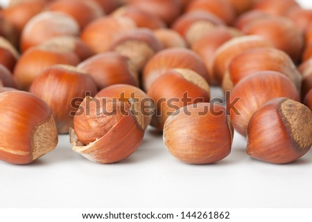 peeled hazelnut among unpeeled, isolated on white background - stock photo