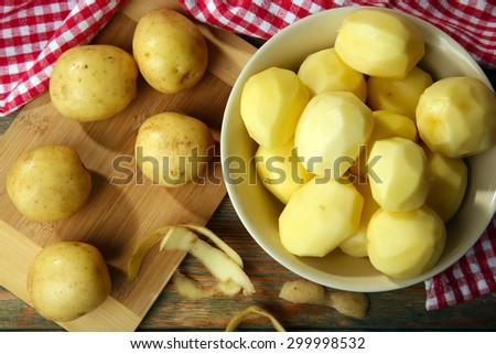 Peeled new potatoes in bowl on wooden table with napkin, top view - stock photo
