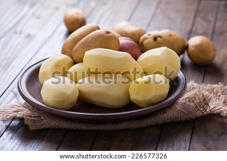 Peeled potatoes in bowl on wooden table. Selective focus.