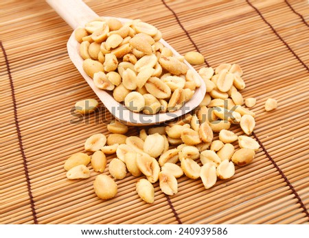 Peeled salted peanuts isolated and wooden spoon on bamboo mat - stock photo