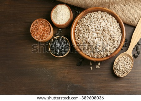 Peeled sunflower, flax and sesame seeds on wooden table background, closeup - stock photo