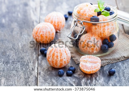 peeled  tangerine or mandarin fruit and blueberry in glass jar on wooden table  - stock photo