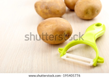 Peeler and potatoes on wooden table - stock photo