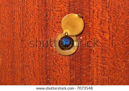 Peephole on peeling wooden door - stock photo