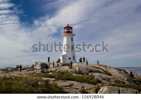 PEGGY'S COVE,NOVA SCOTIA,CANADA-OCTOBER 2: Visitors climb the granite rocks near the lighthouse on October 2, 2013. Peggy's cove lighthouse has a post office inside of it.