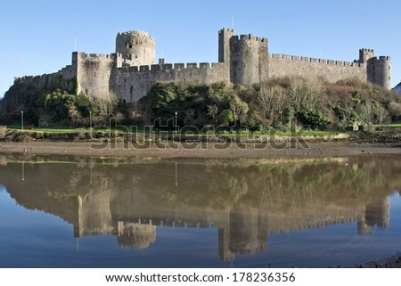 PEMBROKE, UK - DECEMBER 28: Pembroke castle standing high above the modern town centre on December 28, 2013 in Pembroke. The first castle was built around 1093 and remained in use until the mid 17thC - stock photo