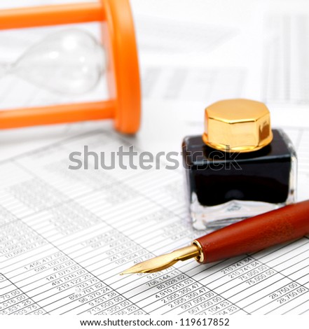 Pen, a sand-glass, and ink on documents. - stock photo