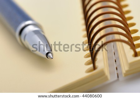 Pen and a notebook on a spiral with a yellow paper. Selective focus - stock photo