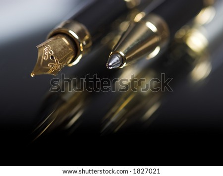 Pen and ballpoint reflected on a shiny surface