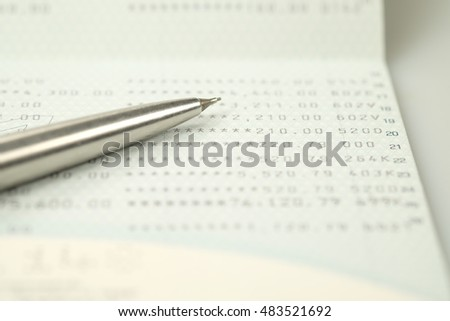 Pen and bank book on white background