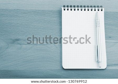 Pen and blank note pad on wooden background - stock photo