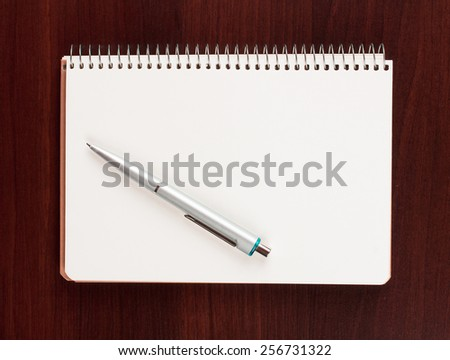 pen and blank paper on wood - stock photo