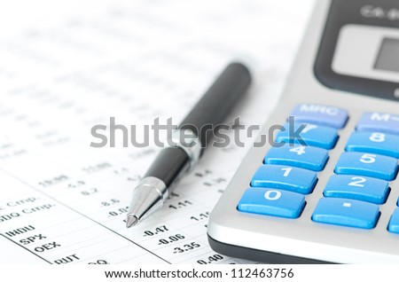 pen and calculator on a chart background - stock photo