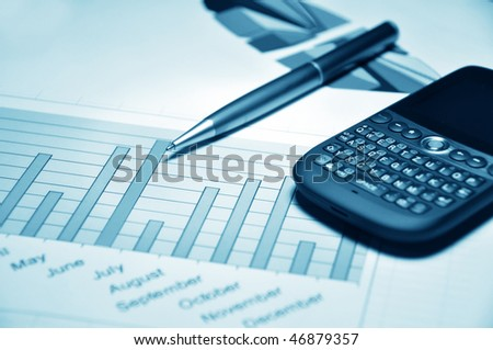 Pen and cell phone on a market report - stock photo