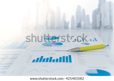 Pen and chart analysis business report on desk of funds manager. - stock photo