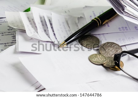 Pen and coins on a lot  of receipts - stock photo