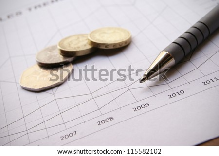 Pen and coins on Financial Chart with positive growth pattern - stock photo
