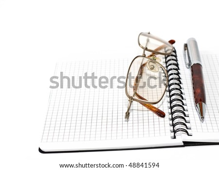 Pen and glasses lying on opened notebook - stock photo