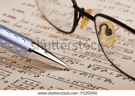 pen and glasses over a math sheet - stock photo