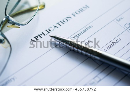pen and glasses over application form