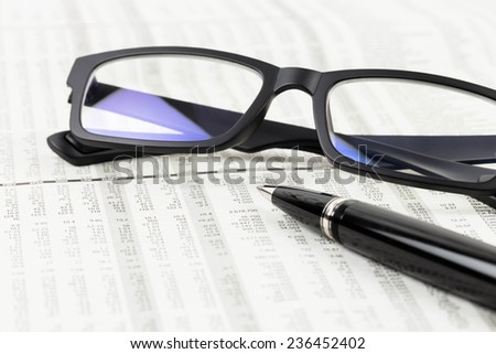 Pen and glasses rest on stock price detail financial newspaper - stock photo