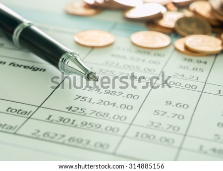 pen and golden coins on summary report. selective focus. - stock photo