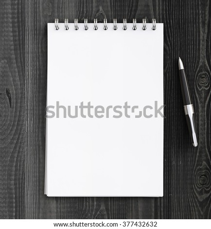 pen and notebook on a wooden table - stock photo