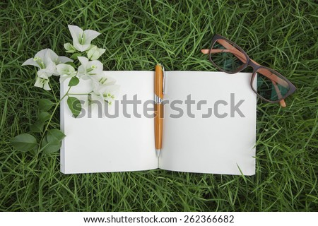 Pen and notebook on the grass
