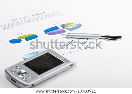pen and pda laying on report with diagrams - stock photo