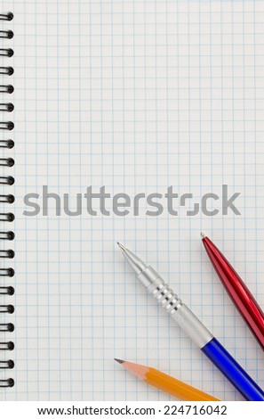 pen and pencil at checked paper of notebook - stock photo