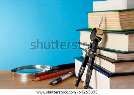 pen, big pile of books and magnifying glass on wood table - stock photo