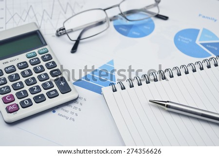 Pen book glasses and calculator on financial chart and graph, accounting background - stock photo