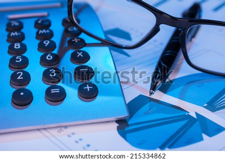 Pen, calculator and glasses in the blue light of the monitor,can be used as background  - stock photo