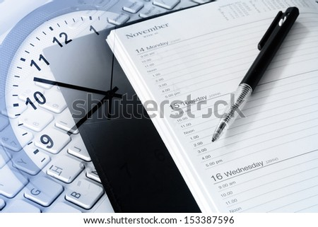 Pen, diary, clock and computer keyboard  - stock photo
