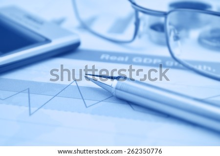 Pen gasses and calculator on financial chart and graph, accounting background - stock photo