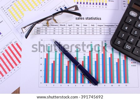 Pen, glasses and calculator on financial chart, business concept, analysis of sales plan, business report, business work station with paperwork - stock photo