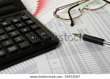 Pen, glasses and calculator on the financial papers