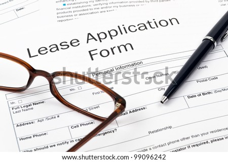 Pen, Glasses and Lease Application Form on desktop in business office.