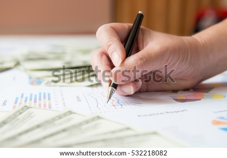 pen in hand and graph background, businesswoman sitting working at her desk in the office checking and analysing a report. Accounting